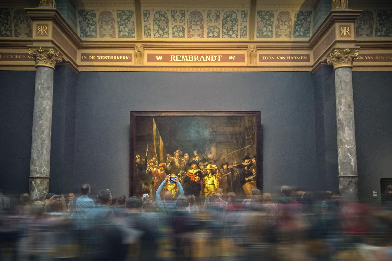 Art gallery with Rembrandt van Rijn's 'The Night Watch' (1642) visible beyond a blurred crowd of visitors