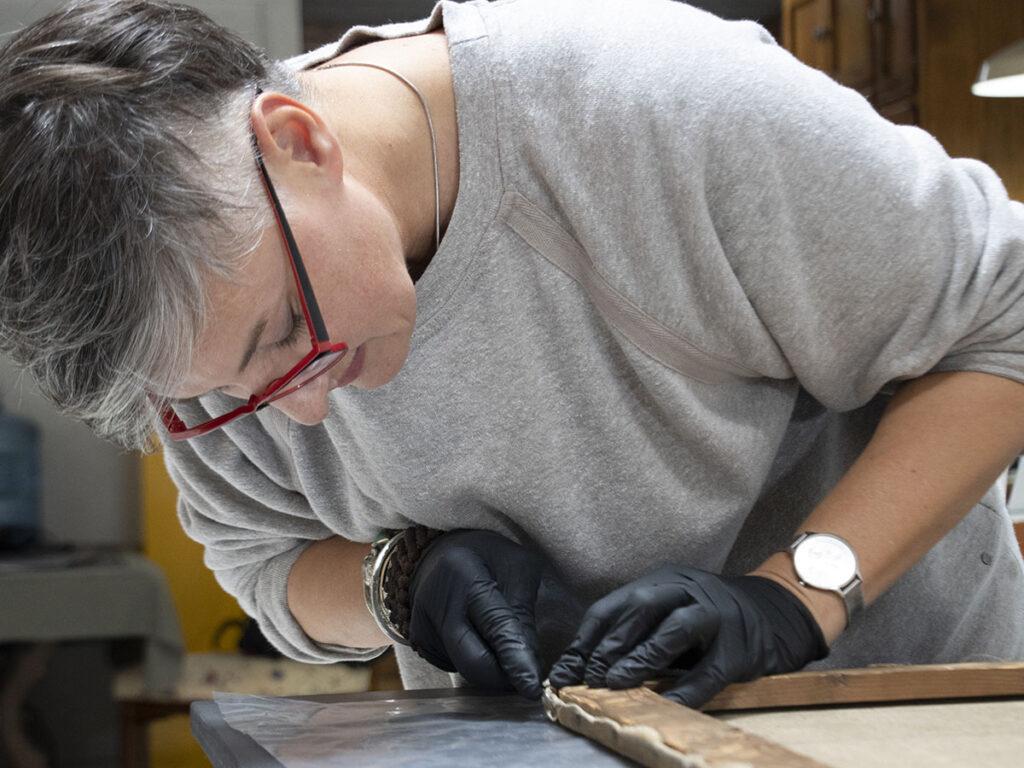 Blanka Kielb, conservator, examining a canvas painting