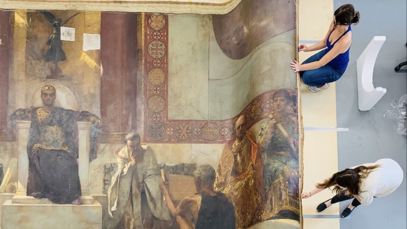 ArtCare conservator and trainee perform treatment on Jean-Joseph Benjamin-Constant's 'Emperor Justinian' during the Conserving Canvas training residency