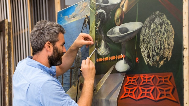 CEO/Director and Partner, Oliver Watkiss, performs conservation treatment on Salvador Dali's 'Nature Morte Vivant (Still Life Fast Moving)'