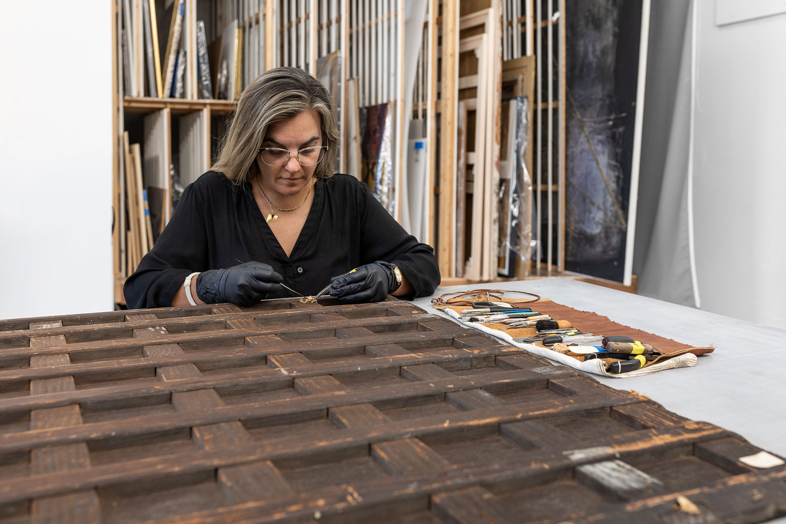 Chief Conservator and Partner, Veronica Romero, performs conservation treatment